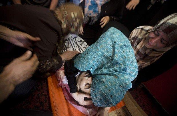 7月12日に殺されたマフムード・スウェイティ(20歳)の遺体に寄り添う母と妹。