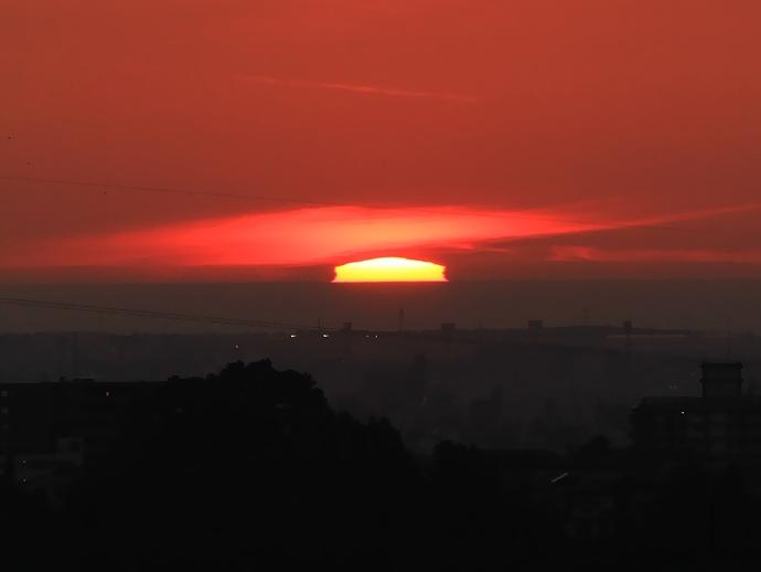 梅雨明けの日 大きく変形した夕日(金沢市太陽が丘にて)