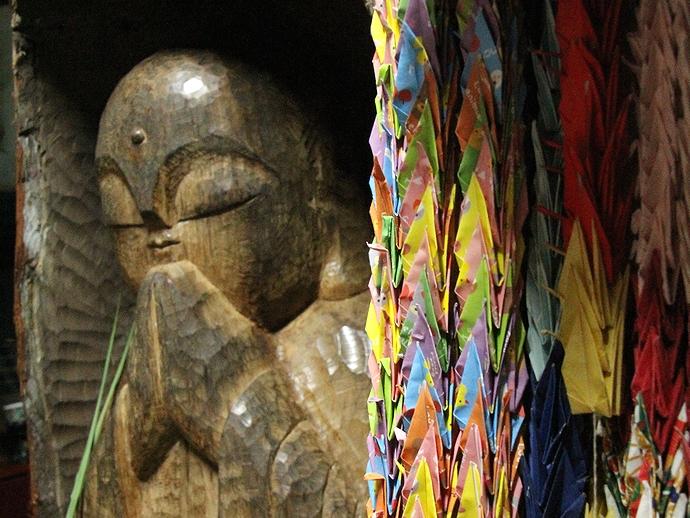 木彫りの像 折鶴とともに(金沢市大乗寺にて)