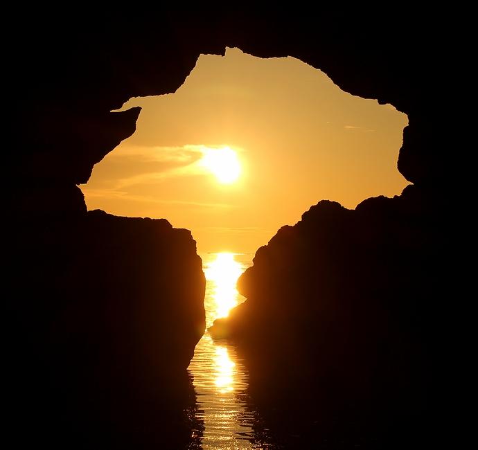 機具岩の夕日のワンシーン 洞門・夕日・輝く海