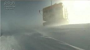 南極 地吹雪の中進む雪上車