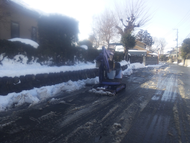 排土板で雪を除雪するユンボ