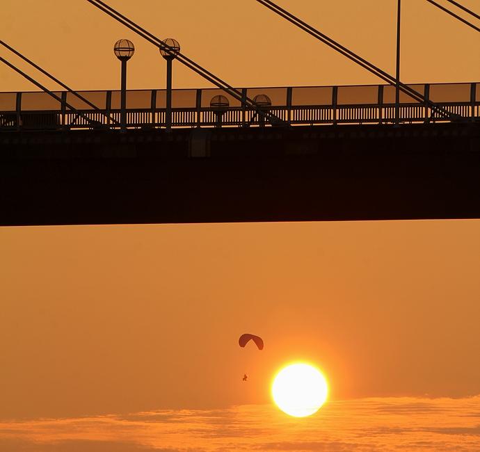 夕日とパラセイリングのシルエット(サンセットブリッジ内灘)
